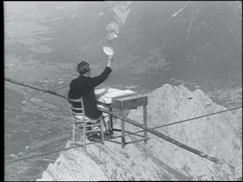 B/W 1920s REAR VIEW man holding pole sitting in chair at table balancing on tightrope over Alps