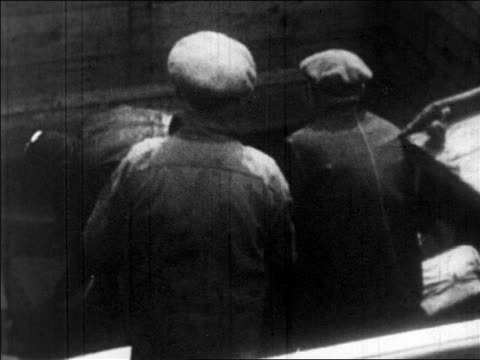 B/W 1920s REAR VIEW men moving boxes on ship smuggling bootleg liquor / Prohibition / newsreel
