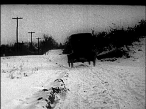 b/w 1920s rear view model t car driving down country road in winter / newsreel - フォード・t型モデル点の映像素材/bロール