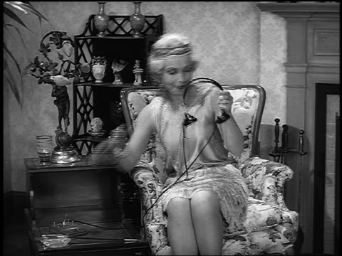 b/w 1920s re-enactment blond flapper sitting in chair putting on headphones + bouncing to music - radio stock videos & royalty-free footage
