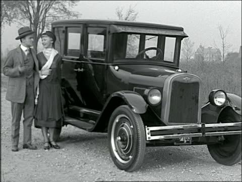 vidéos et rushes de b/w 1920s reenactment couple gets into parked chevrolet + drives off - chevrolet