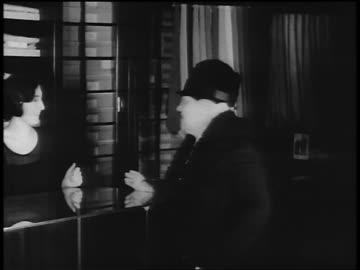 vídeos y material grabado en eventos de stock de b/w 1920s saleswoman showing senior woman mens shirts in clothing store / newsreel - gran almacén