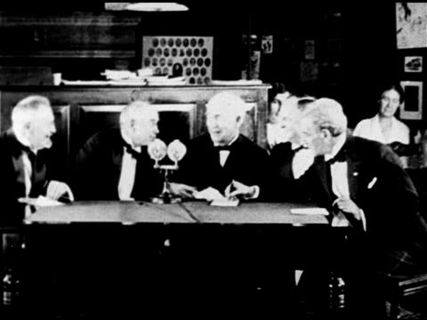 SCIENCE Scientist inventor Thomas Alva Edison sitting at table w/ other elder friends colleagues CU Thomas talking MS Thomas sitting