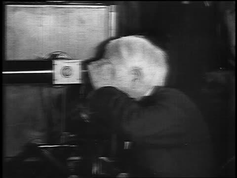 B/W 1920s senior Thomas Edison looking thru scope talking to man in GE factory / slate at end