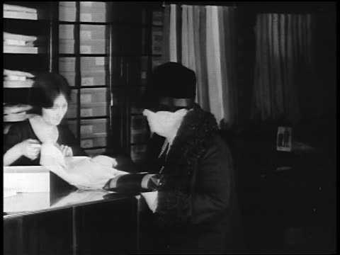 B/W 1920s senior woman buying man's dress shirt from saleswoman in clothing store / newsreel