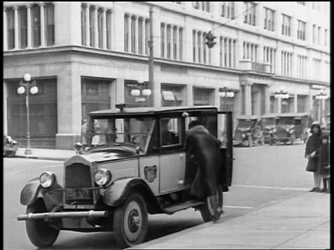 vidéos et rushes de b/w 1920s senior woman getting into taxi on city street / newsreel - taxi