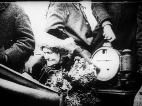 vídeos de stock, filmes e b-roll de b/w 1920s senior woman in hat holding flowers sitting in convertible / documentary - só uma mulher idosa