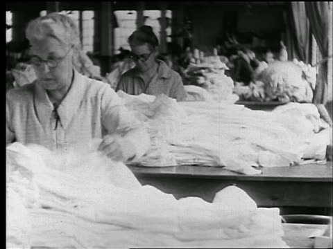 b/w 1920s senior women inspecting piles of shirts in clothing factory / newsreel - textile stock-videos und b-roll-filmmaterial