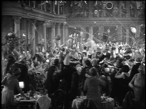 B/W 1920s slow motion high angle wide shot crowd of people in party hats throwing streamers, blowing horns in ballroom
