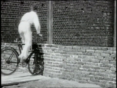 B/W 1920s slow motion (HIGH SPEED) man on bicycle crashing into brick wall, breaking it + falling