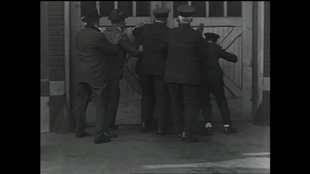 group of policemen 'storming' double doors of garage, pulling smiling man out of building, carrying large still out & sitting down. silly, wacky,... - 1920 stock videos & royalty-free footage