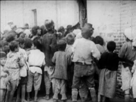vídeos y material grabado en eventos de stock de b/w 1920s starving children crowding door of orphanage / newsreel - orfanato