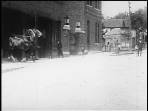 vidéos et rushes de b/w 1920s three horse-drawn fire wagons exiting fire station + speeding away / brooklyn, new york - voiture attelée