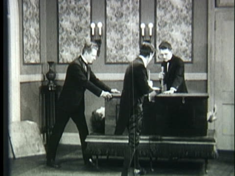 vídeos de stock, filmes e b-roll de 1920s ws three magicians sawing woman in half - mágico