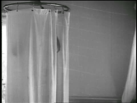 B/W 1920s tilt up man taking shower / educational