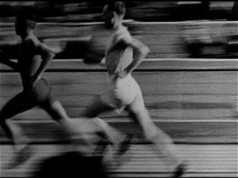 TRACK AND FIELD MS TRACKING Finnish runner Paavo Nurmi racing in race checking stopwatch in hand WS Finish line w/ photographers FG Paavo Nurmi...