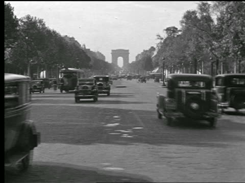 b/w 1920s traffic on tree-lined avenue des champs-elysees / arc de triomphe in background - arc de triomphe paris stock videos & royalty-free footage