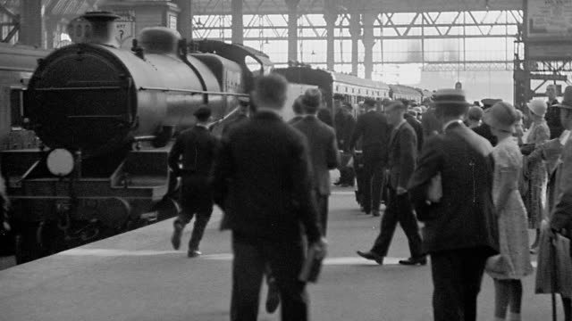 B/W 1920s train arriving in station + passengers walking on platform / London, England