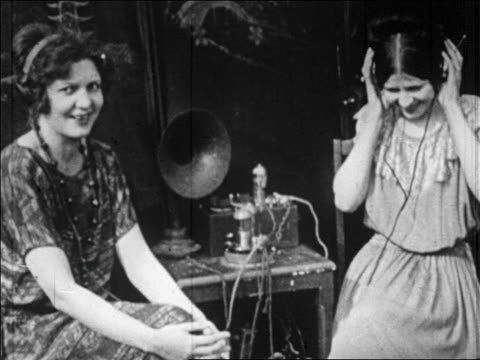 b/w 1920s two women in headphones listening to radio + laughing - 1920 stock-videos und b-roll-filmmaterial
