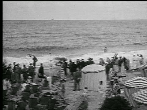 b/w 1920s pan umbrella-tents + crowd of people on beach / people swim in waves / deauville, france - parasol stock videos & royalty-free footage