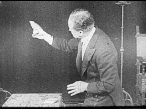 vídeos de stock, filmes e b-roll de vaudeville behind magician harry houdini on stage performing magic sleight of hand card trick cards appearing disappearing in his outstretched hand... - mágico