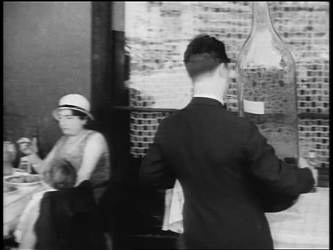 b/w 1920s waiter bringing giant bottle of wine to man at table in outdoor cafe / paris / documentary - 1920 stock-videos und b-roll-filmmaterial