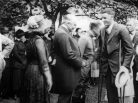 B/W 1920s Warren G Harding standing in line shaking hands with man on crutches / newsreel