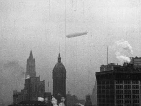 b/w 1920s wide shot graf zeppelin flying over new york city - 飛行船点の映像素材/bロール