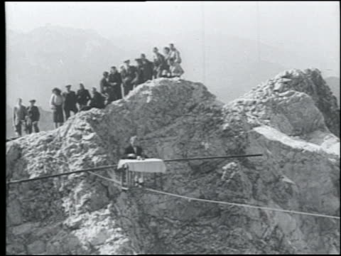 B/W 1920s wide shot man holding pole sitting in chair at table on tightrope over Alps / crowd in background watches