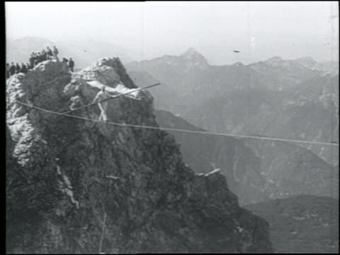 b/w 1920s wide shot man holding pole walking on tightrope above alps - stunt person stock videos & royalty-free footage