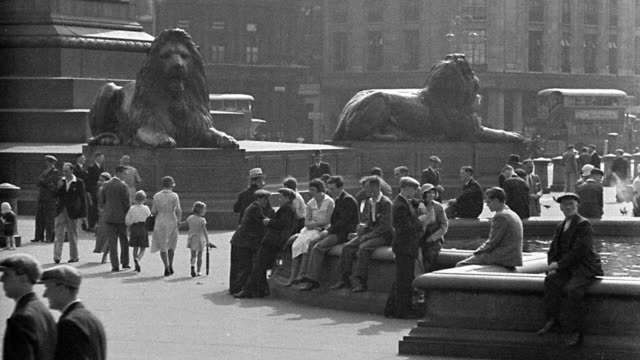 b/w 1920s wide shot people sitting in + walking through trafalgar square with lion statues in background / london - 1920年点の映像素材/bロール