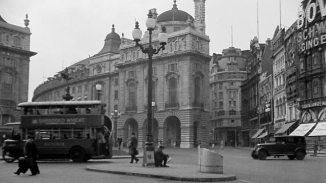 vídeos de stock, filmes e b-roll de b/w 1920s wide shot piccadilly circus traffic scene with buildings + statue / london, england - 1920