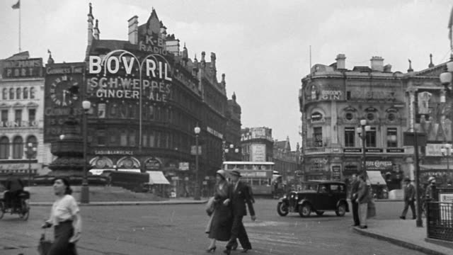 b/w 1920s wide shot piccadilly circus traffic scene with pedestrians + billboard in background / london, england - doppeldeckerbus stock-videos und b-roll-filmmaterial
