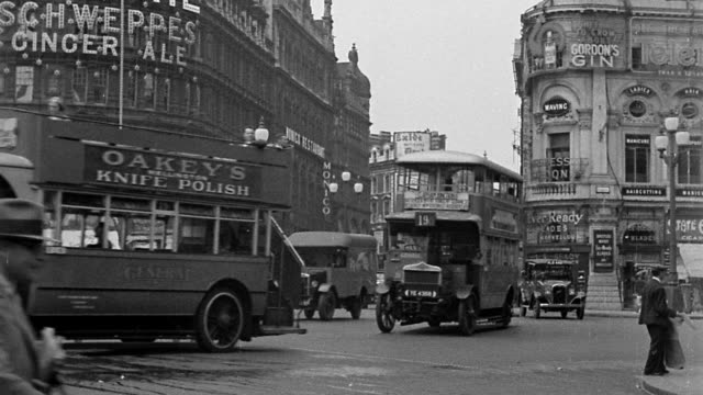 B/W 1920s wide shot Piccadilly Circus traffic scene with pedestrians + billboard in background / London