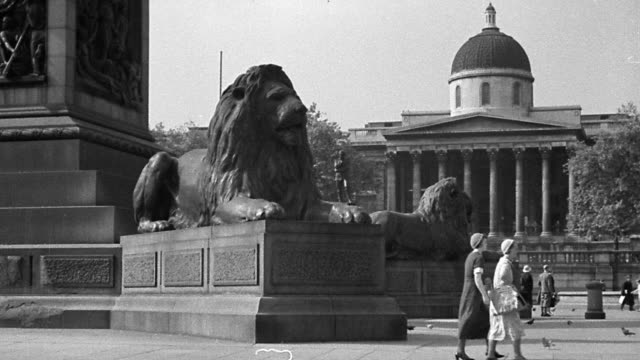 B/W 1920s wide shot Trafalgar Square + National Gallery with lion statues + traffic in foreground / London, England