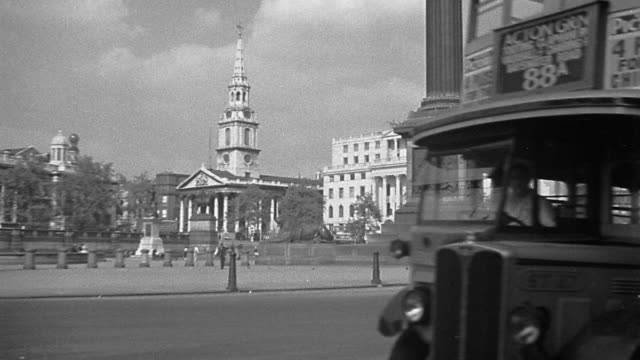 B/W 1920s wide shot Trafalgar square with buses passing + street vendor in foreground / London, England