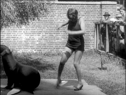 vídeos de stock, filmes e b-roll de b/w 1920s woman in swimsuit doing charleston with seal outdoors - 1920