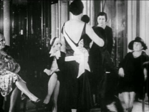 b/w 1920s woman modeling dress for seated women shopping / guerlain, paris / newsreel - haute couture stock videos and b-roll footage