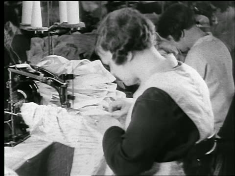 B/W 1920s woman sewing cloth on sewing machine in clothing factory / newsreel