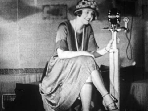 B/W 1920s woman sitting + talking into microphone in radio studio