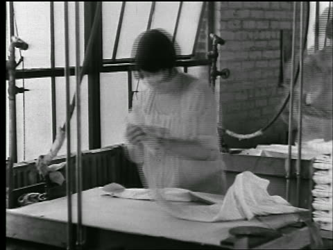 stockvideo's en b-roll-footage met b/w 1920s woman steams, irons + folds shirt in clothing factory /shots dissolve to show time passing - kledingstuk