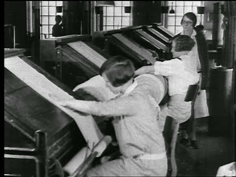 b/w 1920s woman supervises women working at tables with bolts of cloth in textile/clothing factory - 1920年点の映像素材/bロール