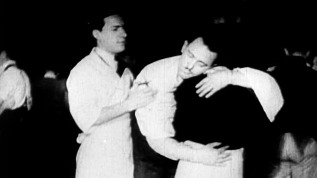 1920s women holding exhausted men up during marathon dance contest couples during marathon dance stunt - 1925年点の映像素材/bロール