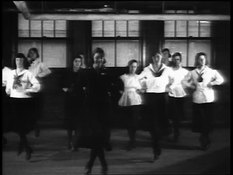 B/W 1920s women in uniforms dancing / working out in vocational school / newsreel