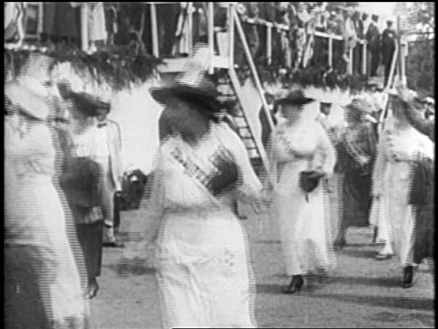 B/W 1920s women suffragettes marching waving flags / newsreel