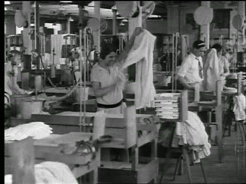 stockvideo's en b-roll-footage met b/w 1920s pan workers folding, packaging + ironing shirts in clothing factory / newsreel - kledingstuk