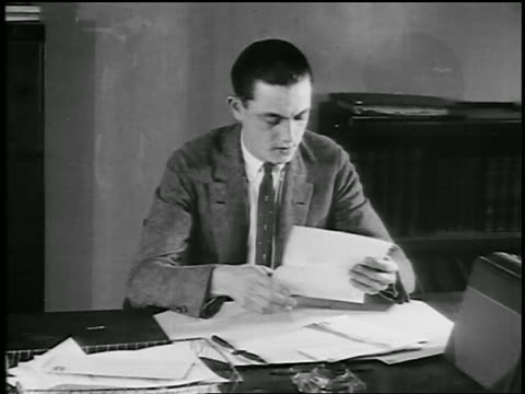 B/W 1920s young man at desk reading letter + rubbing eyes / educational
