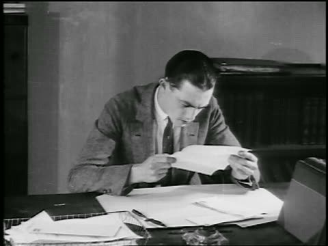 b/w 1920s young man at desk straining to read letter / educational - correspondence stock videos & royalty-free footage