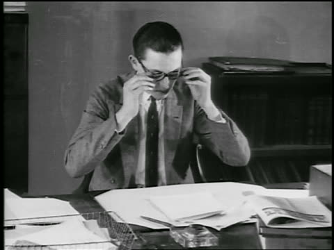 B/W 1920s young man putting on eyeglasses + reading letter at desk / educational