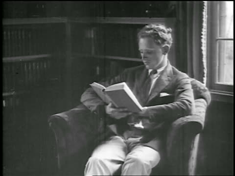 stockvideo's en b-roll-footage met b/w 1920s young man sitting in armchair reading book / educational - 1920